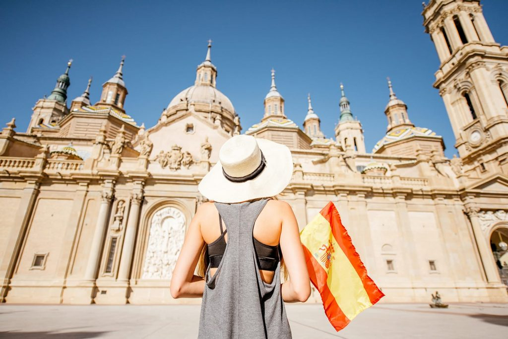 Young woman tourist standing back with spanish flag in front of the famous cathedral on the central square during the sunny weather in Zaragoza city, Spain