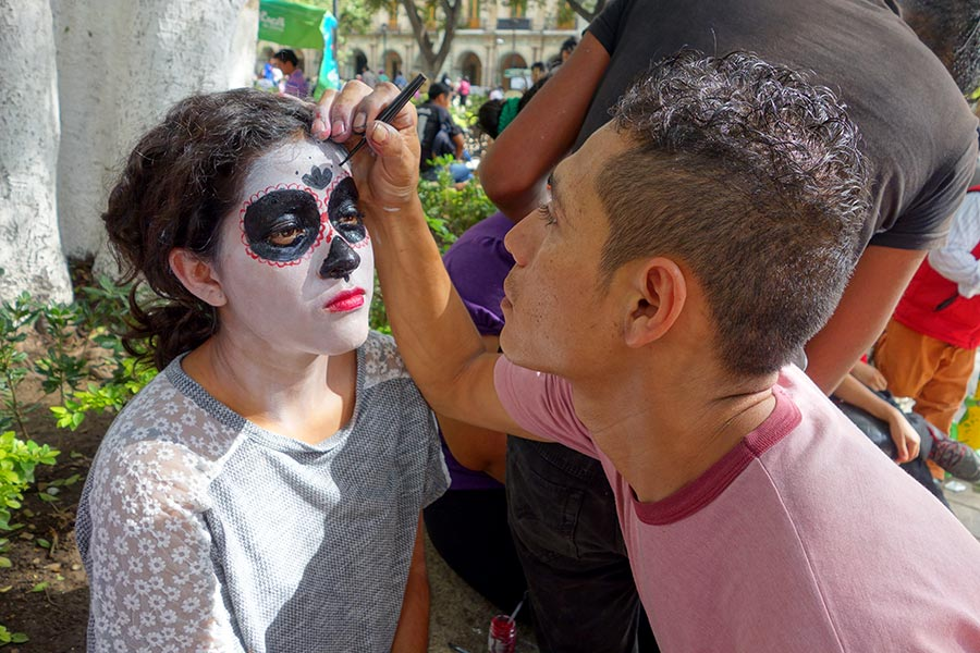 Girl painting her face for the Day of the Dead Celebration in Oaxaca