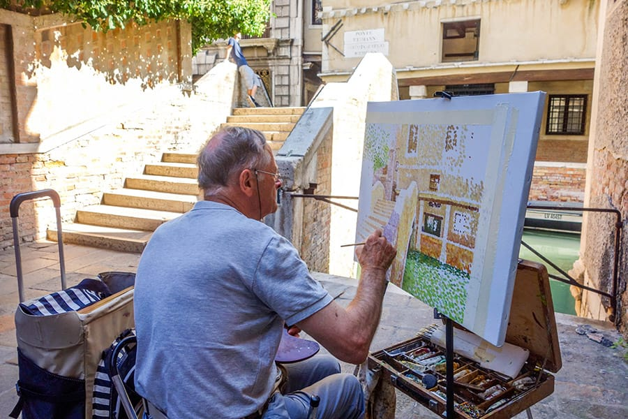 Artist painting one of the beautiful alleyways in Venice