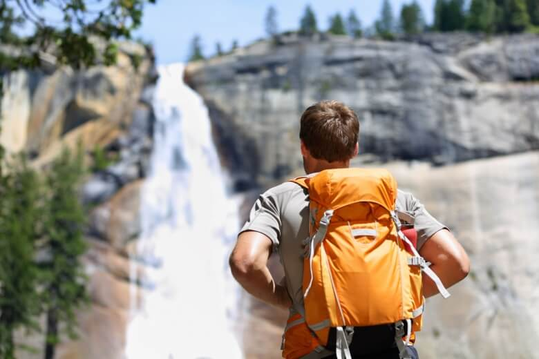 Hiker hiking with backpack looking at waterfall in Yosemite park in beautiful summer nature landscape.