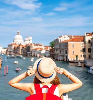 View on Grand canal with woman traveler in hat on Academia bridge in Venice.