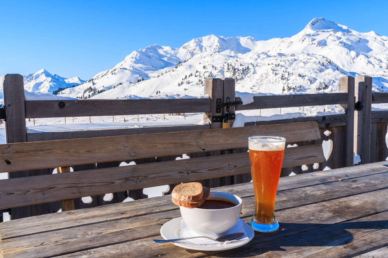 Glass of cold beer and hot soup on wooden table of mountain hut in Obertauern ski area, Austria