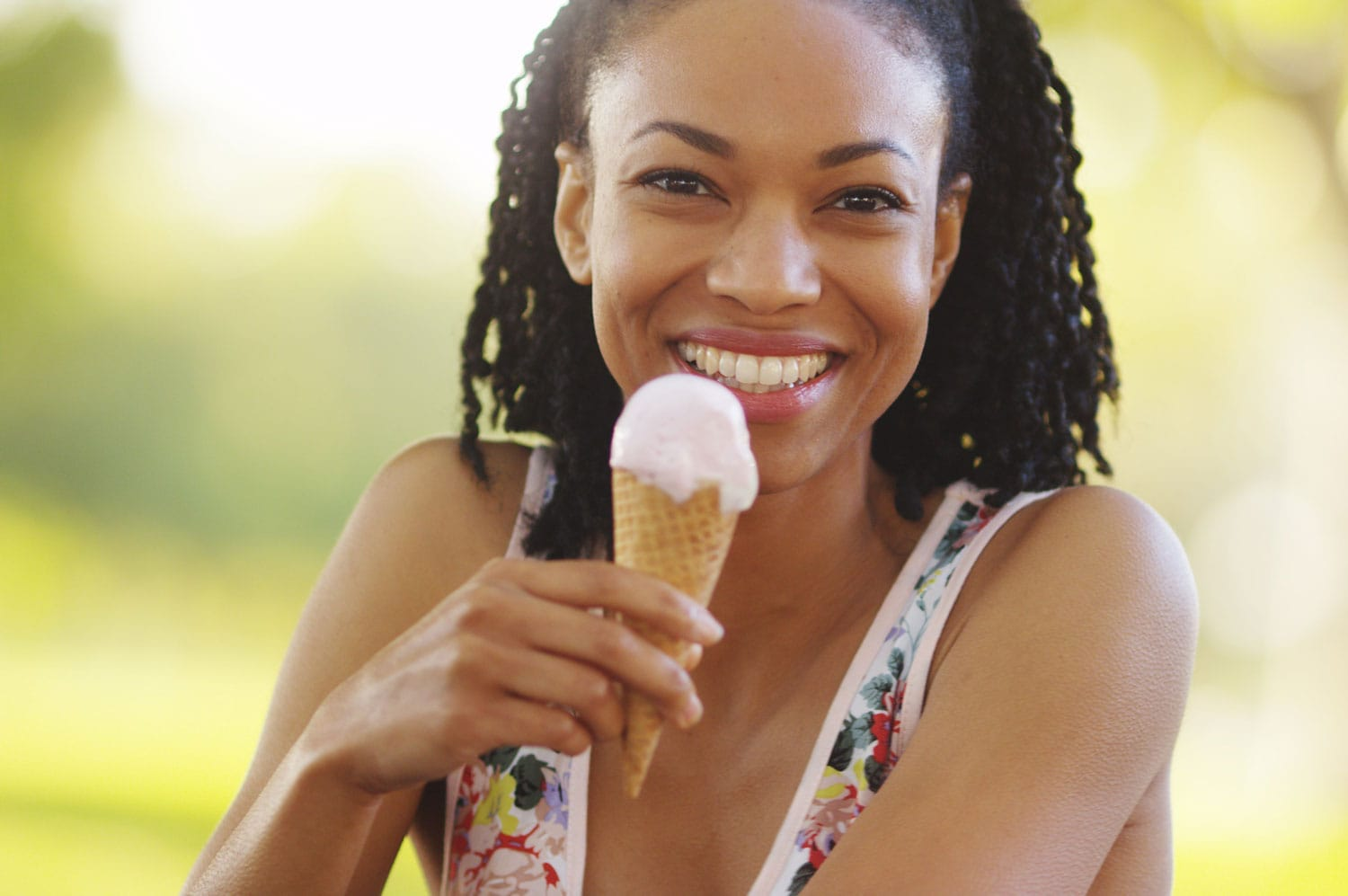 Black woman smiling and eating ice cream