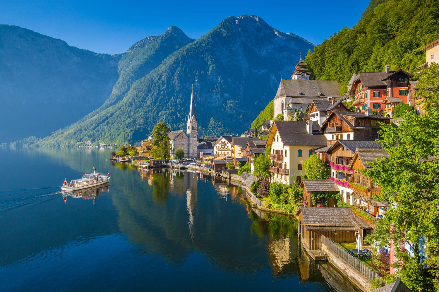 Scenic picture-postcard view of famous Hallstatt lakeside town in the Austrian Alps with passenger ship in beautiful morning light at sunrise on a sunny day in summer, Salzkammergut region, Austria