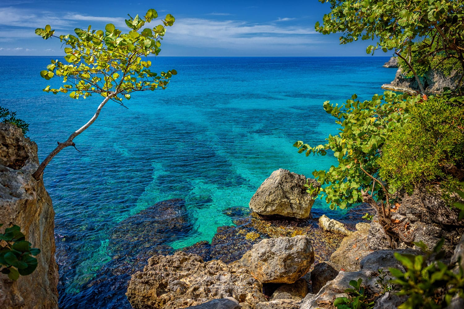 Beautiful turquoise and blue water near rocks and cliffs in Negril, Jamaica.