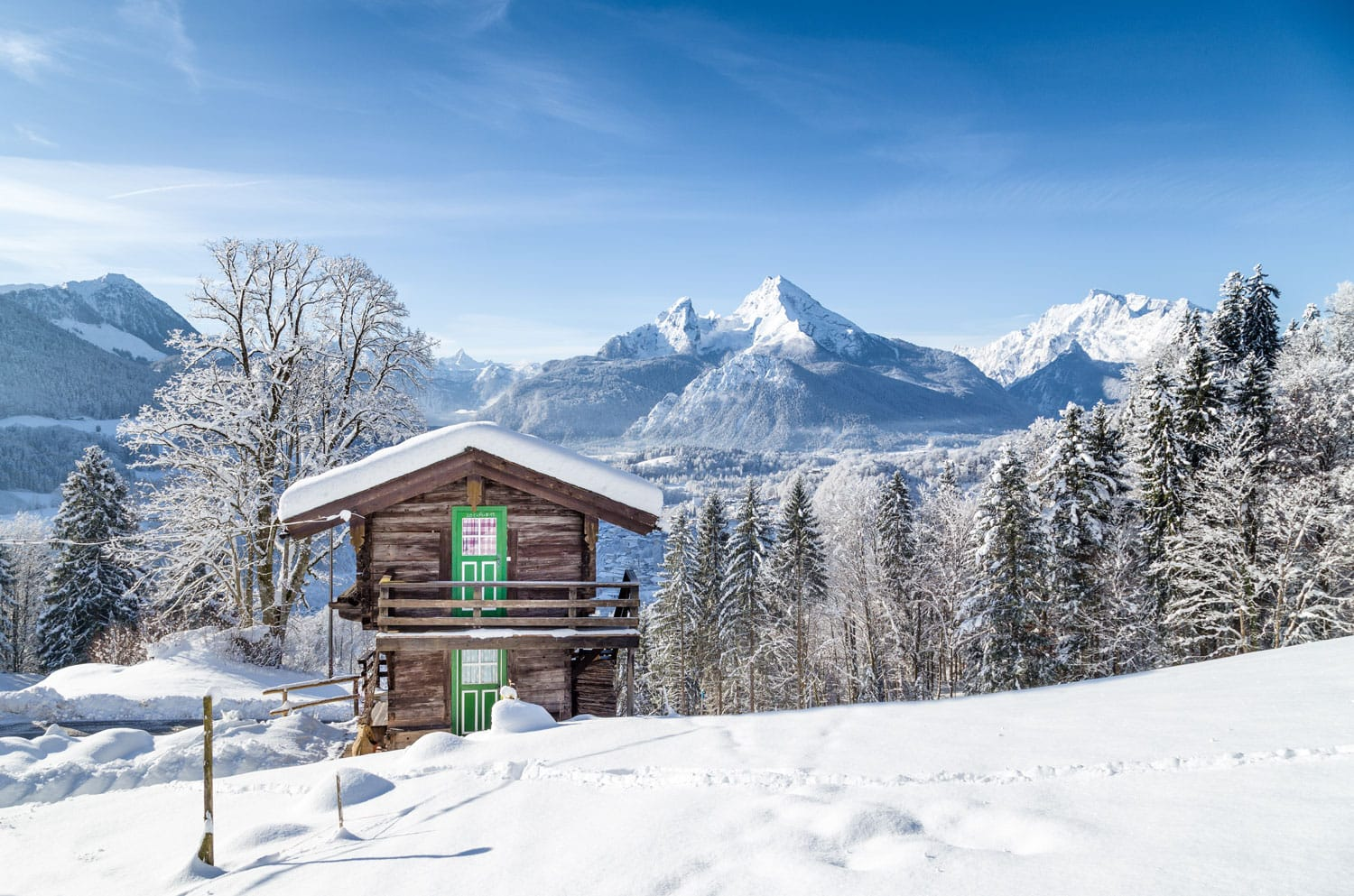 Panoramic view of beautiful white winter wonderland mountain scenery in the Alps with traditional old wooden mountain chalet on a cold sunny day with blue sky and clouds