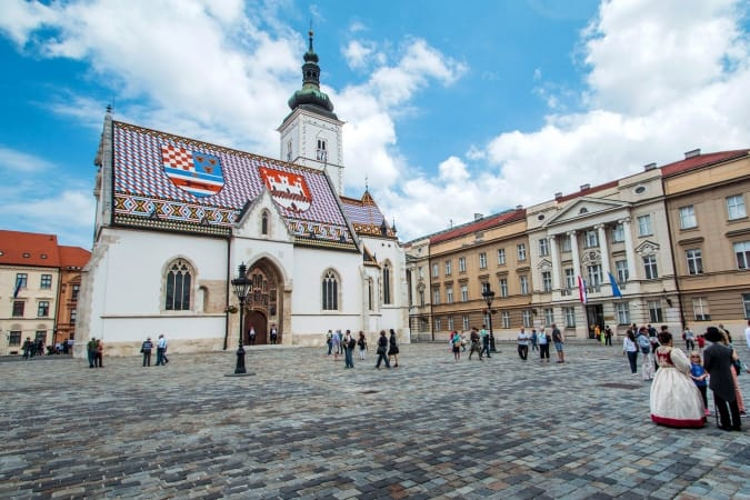 St Mark's Square in Zagreb, Croatia, surrounded by tourists. St Mark's square is political center of Croatia and popular tourist location.