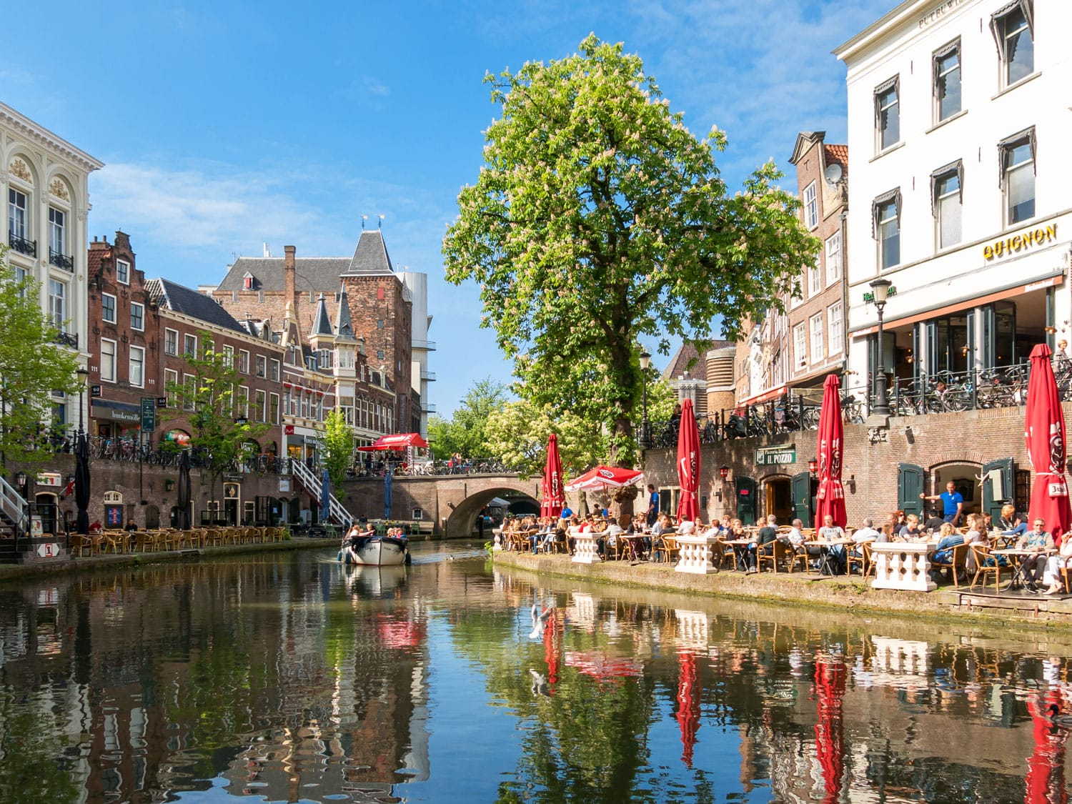 Oudaen Castle and people on outdoor terrace of restaurants alongside Oudegracht canal in the city of Utrecht, Netherlands