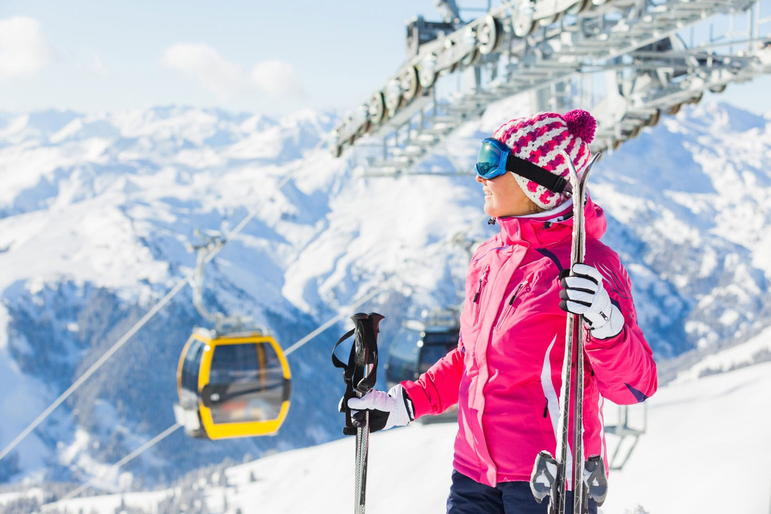Happy woman in ski goggles against a skilift in Zellertal, Austria