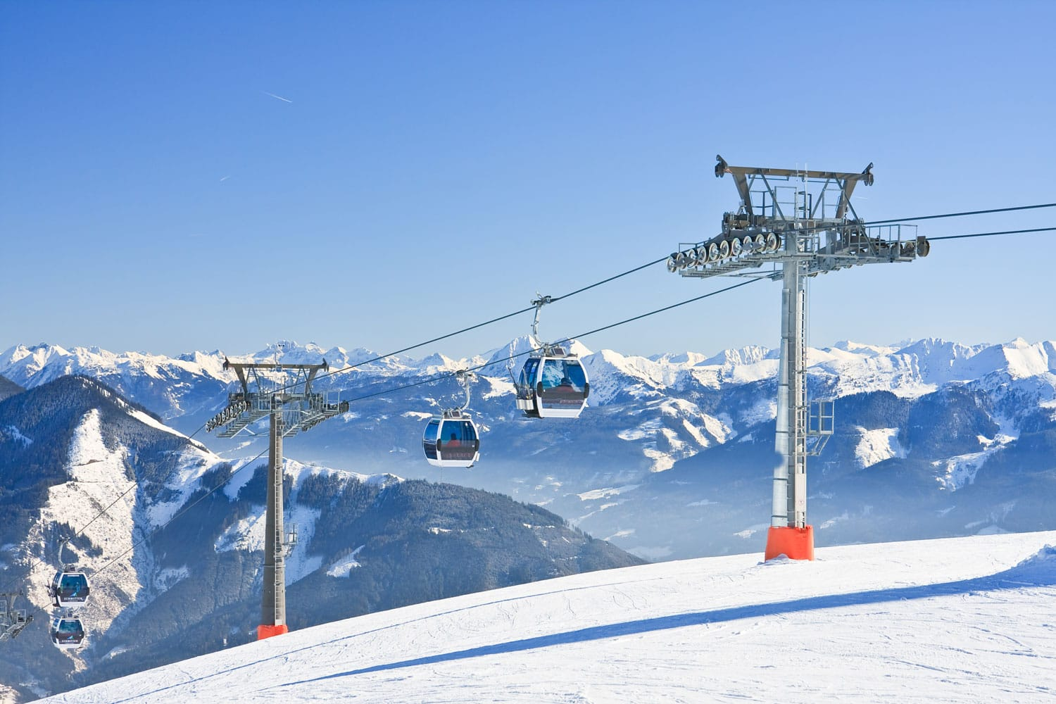 Chairlift cable car and ski slopes in the mountains of Zell am See winter resort, Austrian Alps