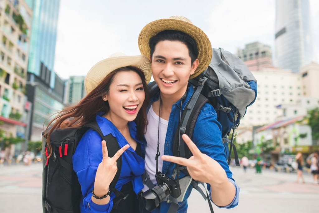young dating couple in city taking photos