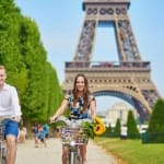 Young romantic couple of tourists using bicycles near the Eiffel tower in Paris, France