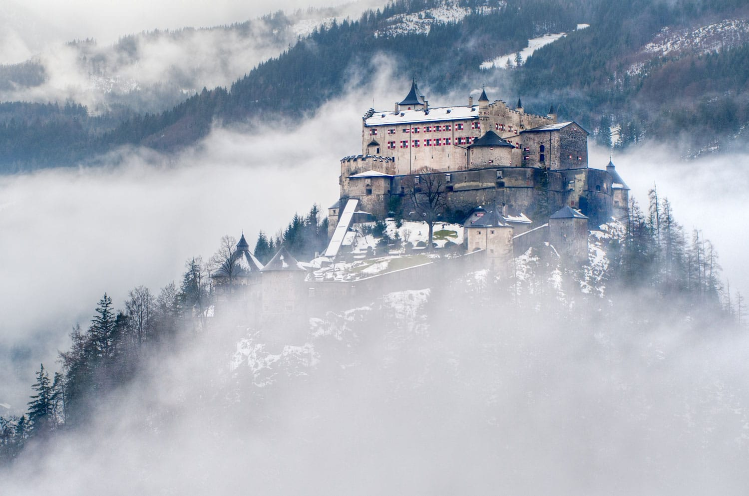 Castle Hohenwerfen by Salzburg high over clouds on a misty mountain in the Alps