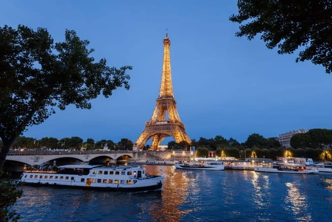 Eiffel Tower, cruise boats and bridge on Seine river at night in Paris, France