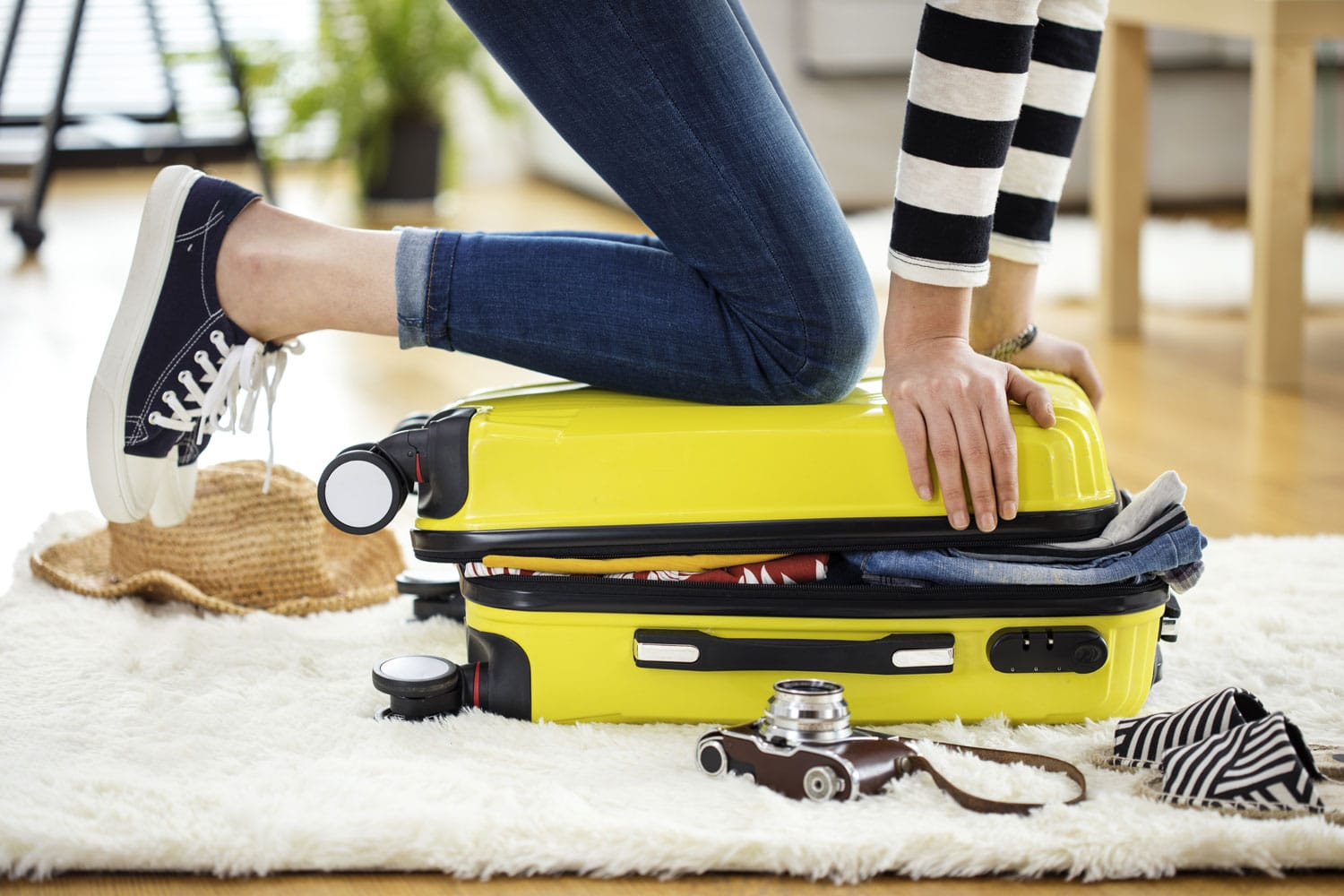 Women trying to close a suitcase