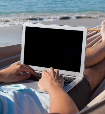 Man using laptop while relaxing on hammock in beach