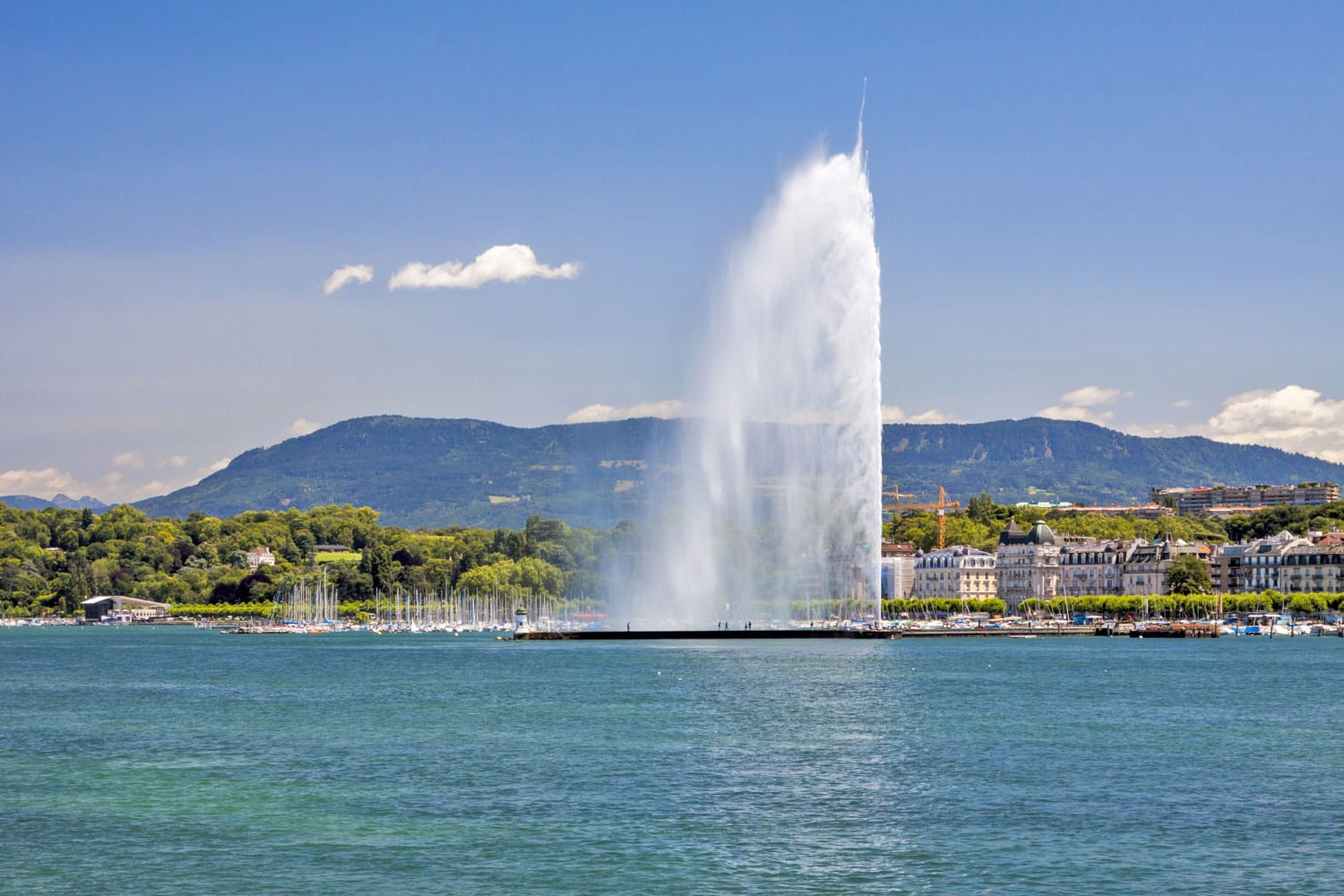Panorama of the southern Lake Geneva shore and of the famous jet d'eau (water jet) fontain in Canton Geneva, Switzerland