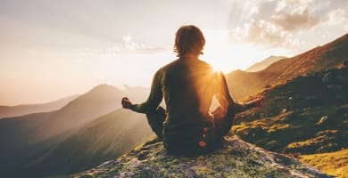 Man meditating on top of a mountains