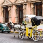 Horse carriages with passengers on a city street in Merida Mexico.