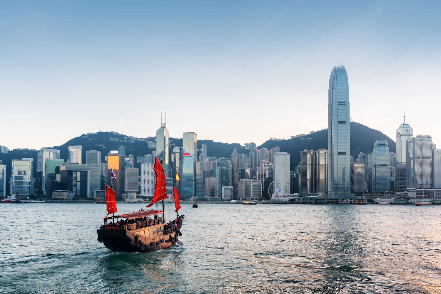 Tourist sailboat crosses Victoria harbor from Kowloon side to the Hong Kong Island
