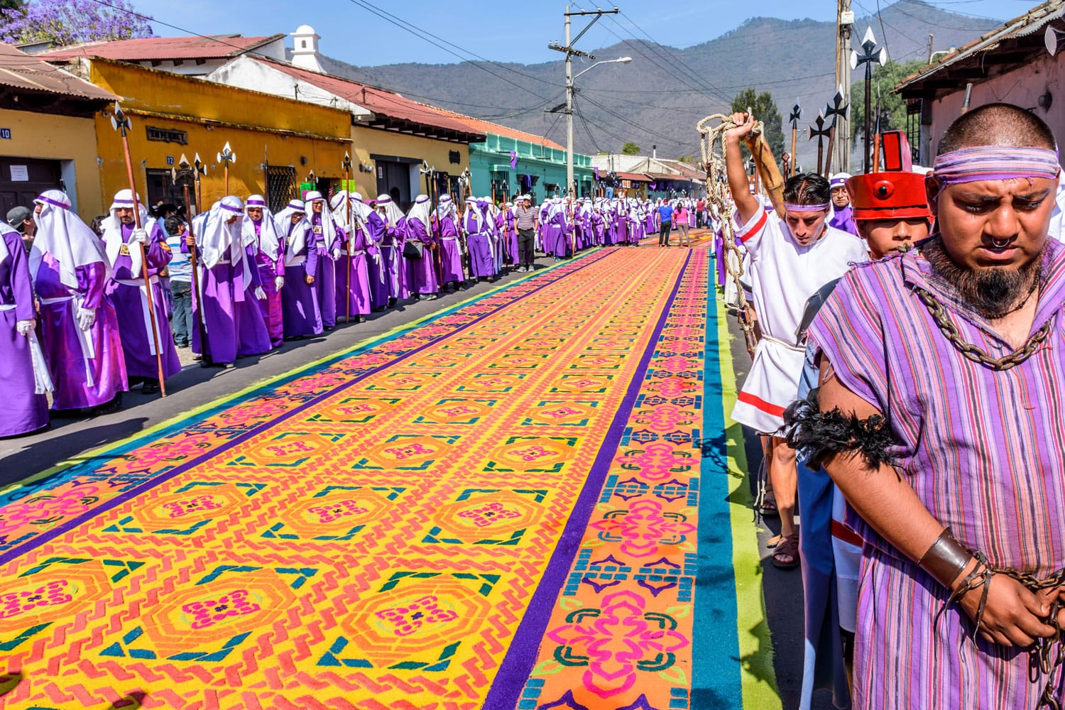 Locals reenact biblical scenes walking over handmade dyed sawdust carpets on Good Friday in colonial town with most famous Holy Week celebrations in Antigua, Guatemala