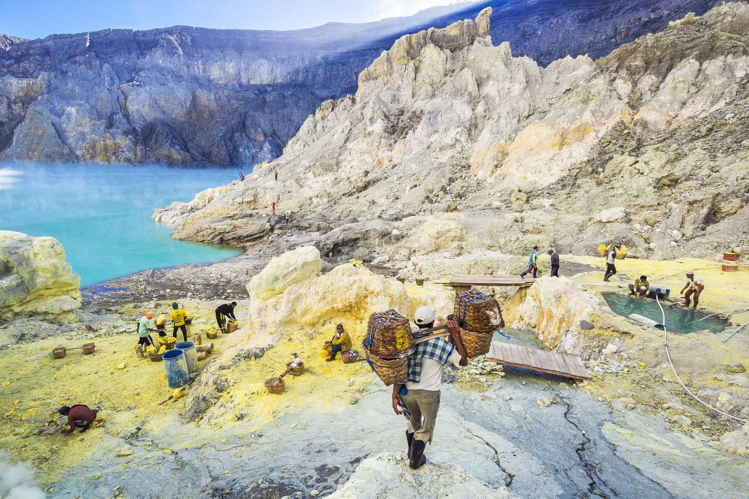 Sulfur miner hiking down into the crater of Kawah Ijen volcano in East Java, Indonesia.
