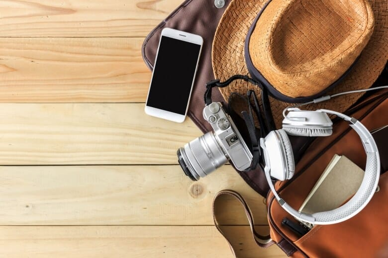 Top view of essential modern. travel accessories on wooden table background