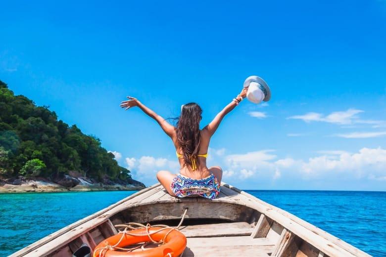 woman in bikini relaxing on wooden boat