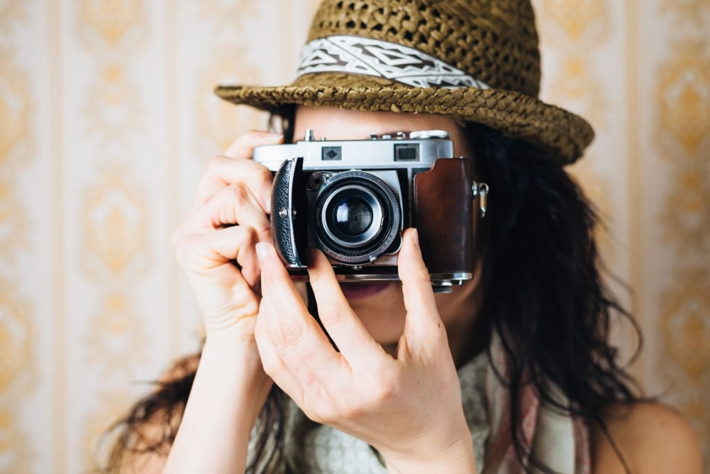 woman taking photos with retro film camera