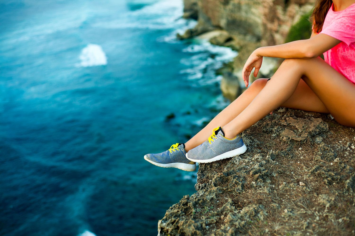 Women sitting on a cliff showcasing her shoes