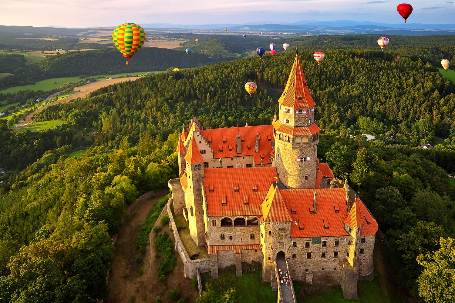 Aerial view on romantic fairy castle with group hot air balloons in picturesque landscape lit by evening sun. Moravia, Czech republic.