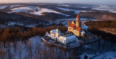Aerial view on romantic fairy castle in winter picturesque winter landscape illuminated by the setting sun. Gothic castle in winter highland surrounded by trees. Bouzov castle, Czech republic.