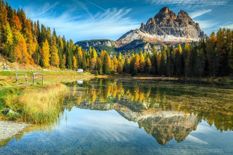 Majestic autumn landscape,alpine glacier lake and yellow pine trees, Antorno lake with famous Tre Cime di Lavaredo peaks in background, Dolomites, Italy, Europe