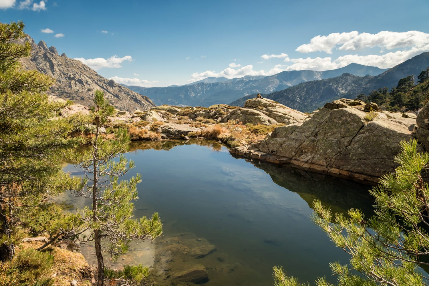 Small lake at Paglia Orba surrounded by rocks, pine trees and mountains near the GR20 hiking trail in central Corsica