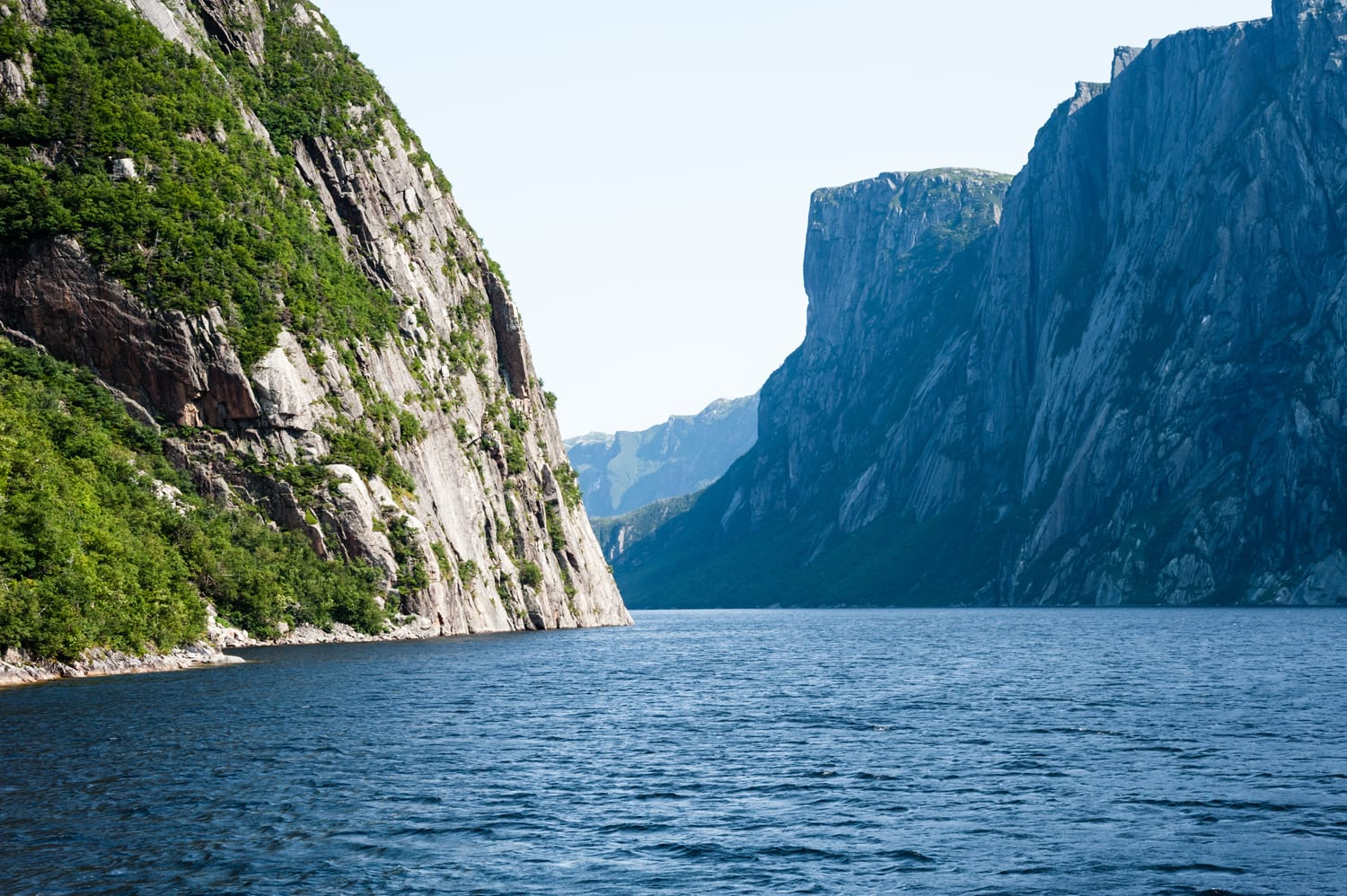 Inland fjord between large steep cliffs with some green vegetation on rock face, at Western Brook Pond, Gros Morne National Park, Newfoundland, Canada.