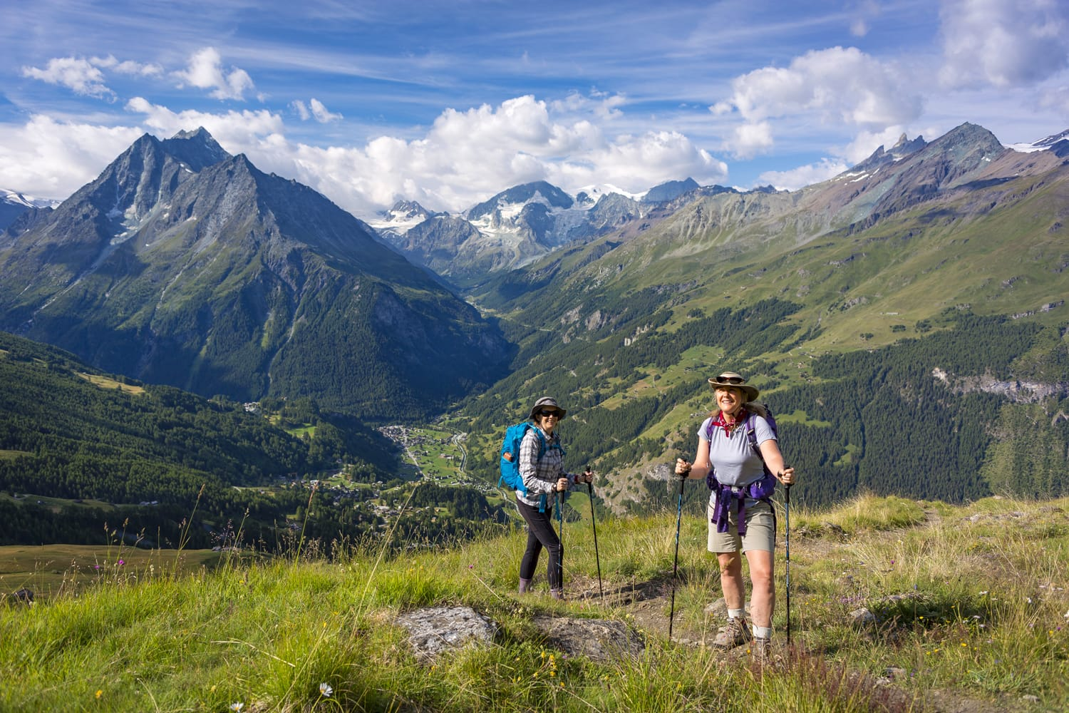 Two women hiking on Haute Route hiking trail, landscape above village of La Sage, Canton of Valais.