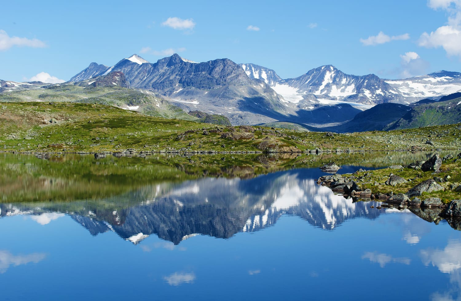Reflection of mountain chain in a small lake in Jotunheimen national park in Norway.