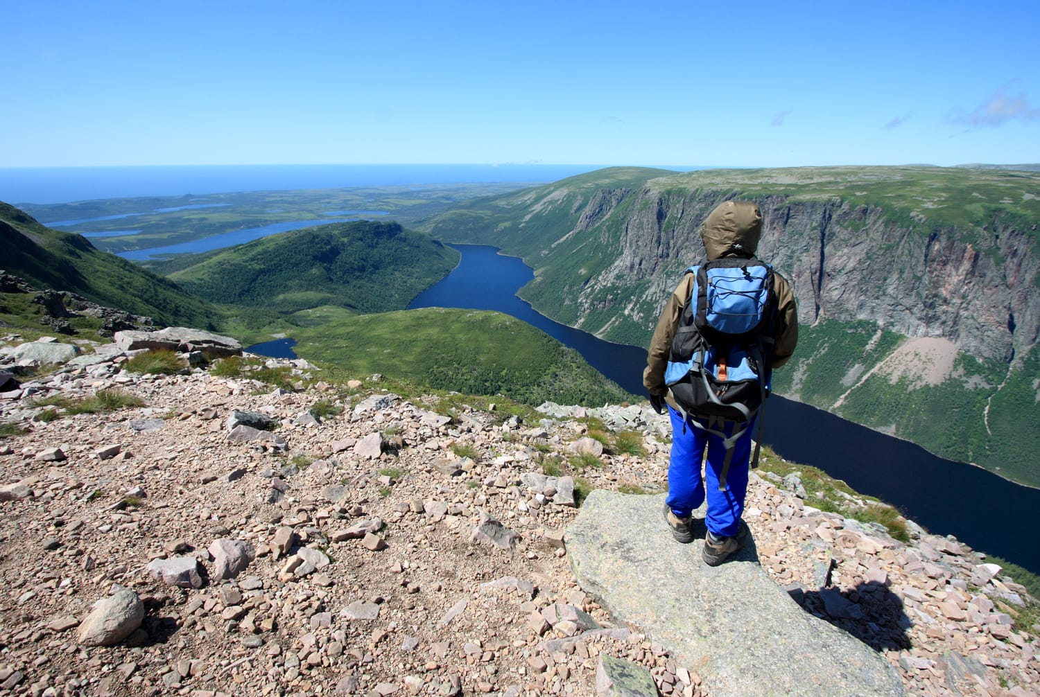 A female hiker standing on Gros Morne Mountain above Ten Mile Pond in Gros Morne National Park, Newfoundland, Canada.