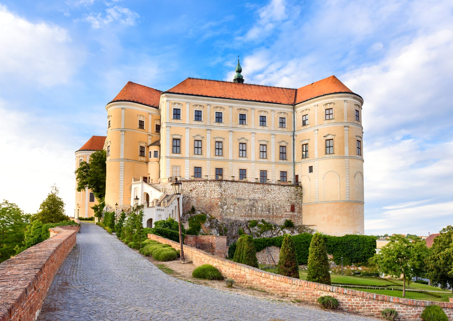Mikulov castle or Mikulov Chateau on top of rock. View from garden of castle with beautiful staircase and bright blue sky with clouds in background. Mikulov, Moravia, Czech Republic.