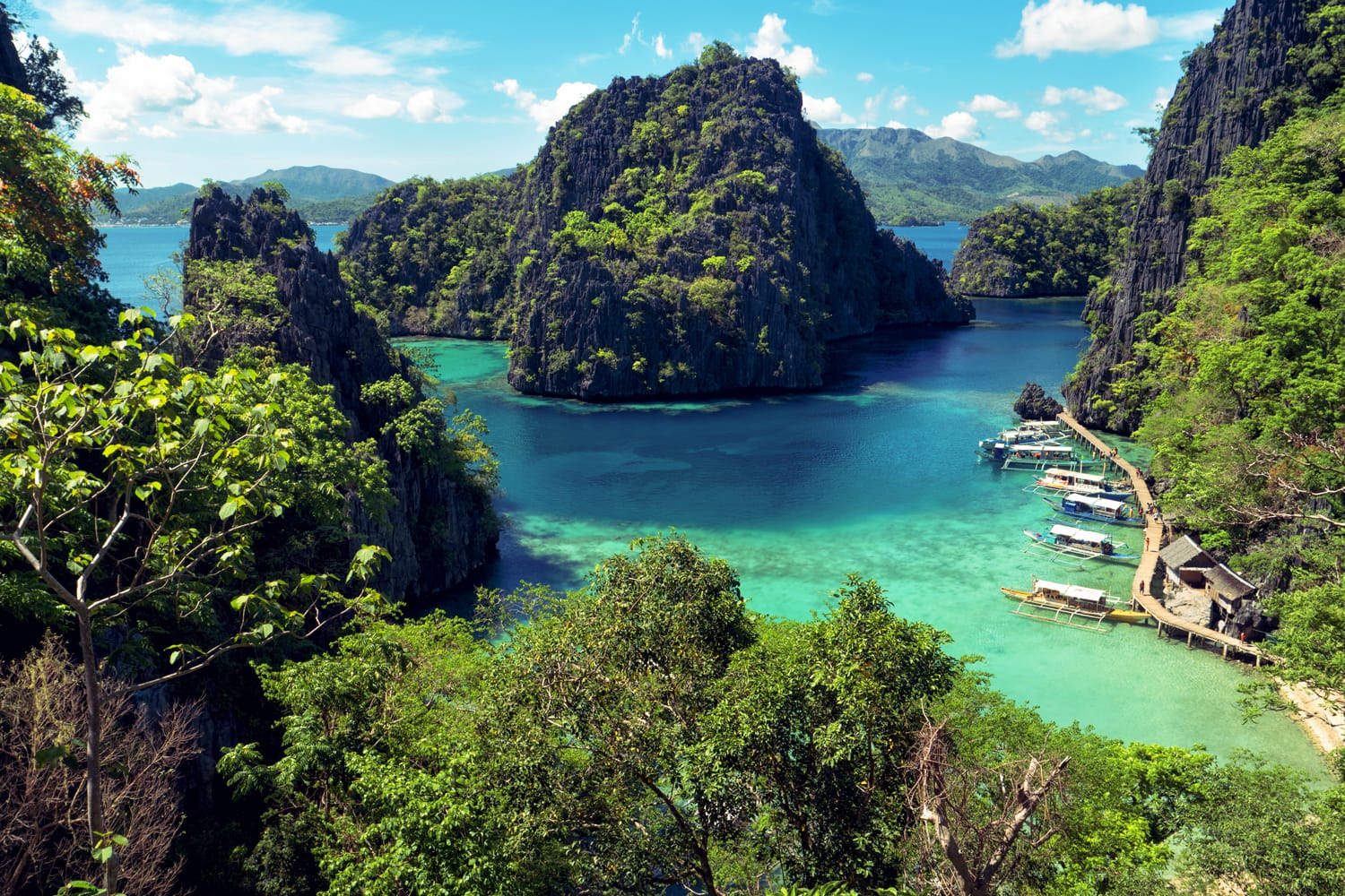 Elevated view of lagoon with boats surrounded by rocks and turquoise sea. Coron. Palawan, Philippines