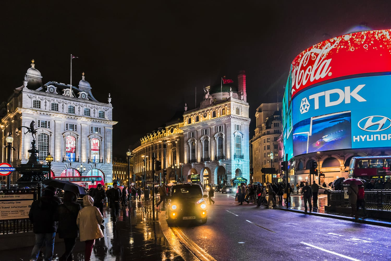 Famous Piccadilly Circus neon signage shines at rainy night. These signs have become a major attraction of London, United Kingdom