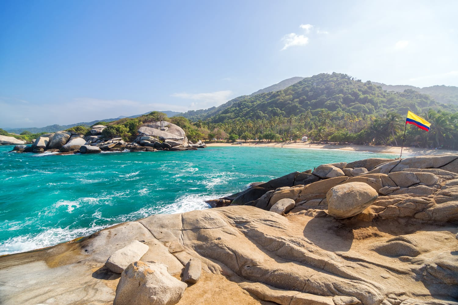 Tropical beach in Tayrona National Park in Colombia with a Colombian flag visible