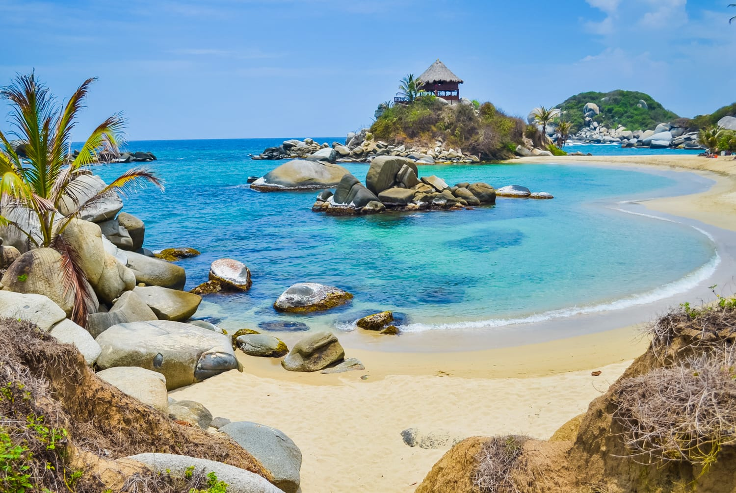 Beautiful bay with white sand beach, blue water and big boulders in Tayrona national park in Colombia