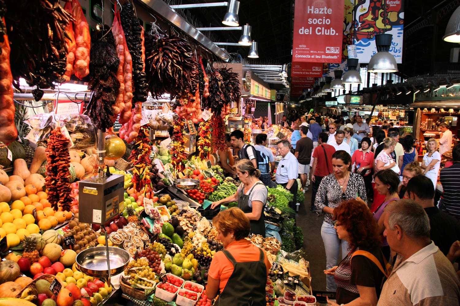 Tourists in famous La Boqueria market in Barcelona. One of the oldest markets in Europe that still exist. Established 1217.