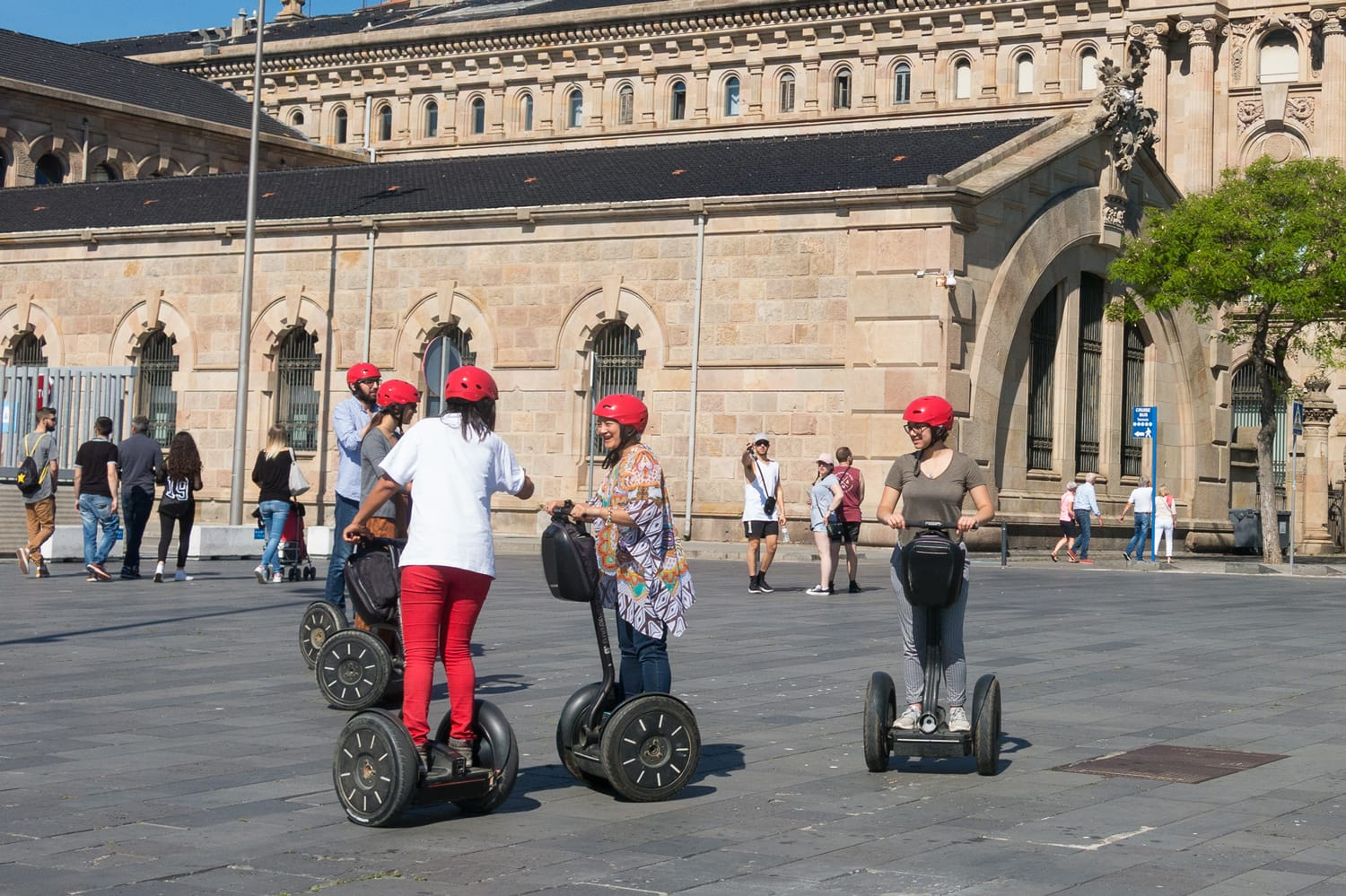 Tourists travel by segway Near the statue of Christopher Columbus at the lower end of La Rambla in Barcelona