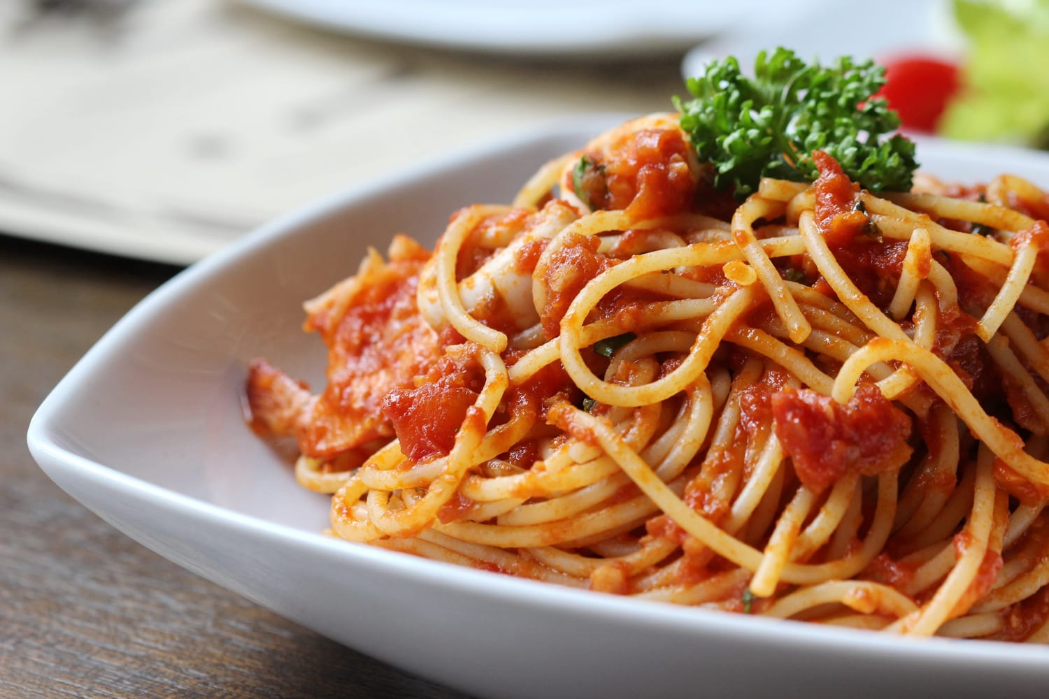 Low angle view of a serving of fresh Italian spaghetti with a meat based bolognese or bolognaise with tomato sauce on a plain white plate