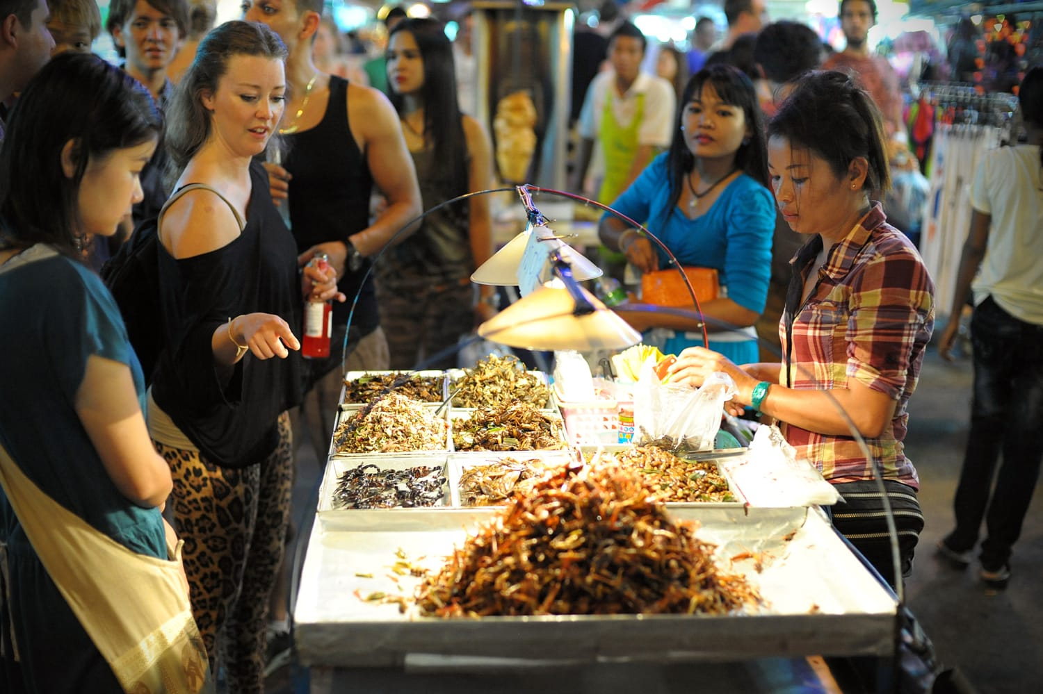 A street vendor sells fried insects to tourists on Khao San Road in Bangkok Thailand