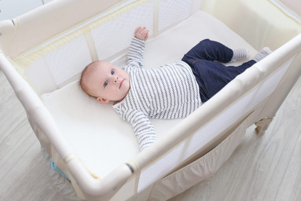 Baby in one of the best travel cribs