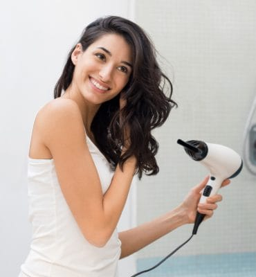 Beautiful girl using a hair dryer and smiling while looking at the mirror. Smiling woman drying hair with hair dry machine.