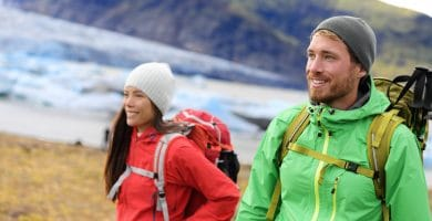 Hiking adventure travel people living active healthy lifestyle wearing jackets and backpacks on Iceland by glacier and glacial lagoon / lake of Fjallsarlon, Vatna glacier, Vatnajokull National Park.